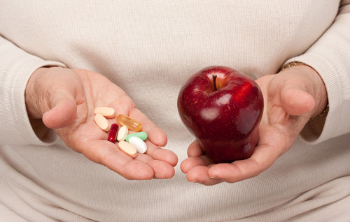 Senior Woman Holding Pills and Apple in her Palms.